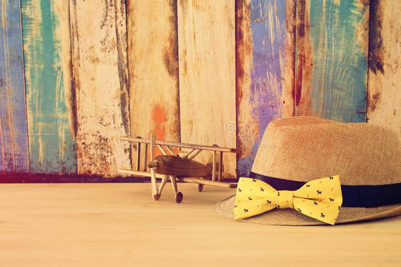 Image of male fedora hat and plane toy over wooden table. Father`s day concept. Image of male fedora hat and plane toy over wooden table. Father`s day concept stock images