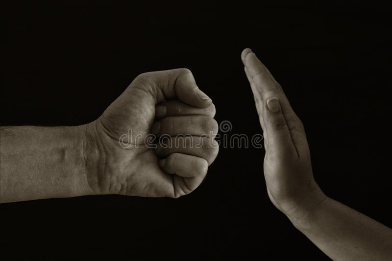 Image of male fist and female hand showing STOP. Domestic violence concept against women. Black and white photo. royalty free stock image