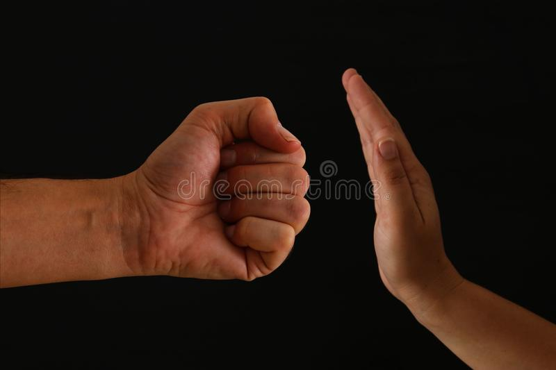 Image of male fist and female hand showing STOP. Domestic violence concept against women. stock photos