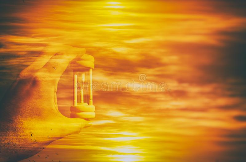 Image of male hand holding hourglass against sky. global warming and ecological problems. double exposure. stock photos