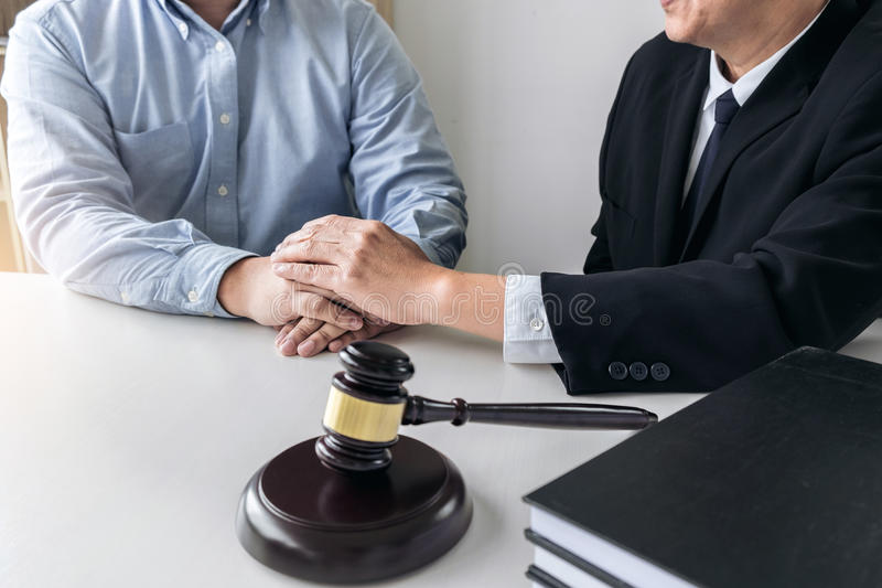 Image of Male lawyer or judge help encourage client, customer, w. Orking with gavel and Law books, report the case on table in modern office, Law and justice royalty free stock photos