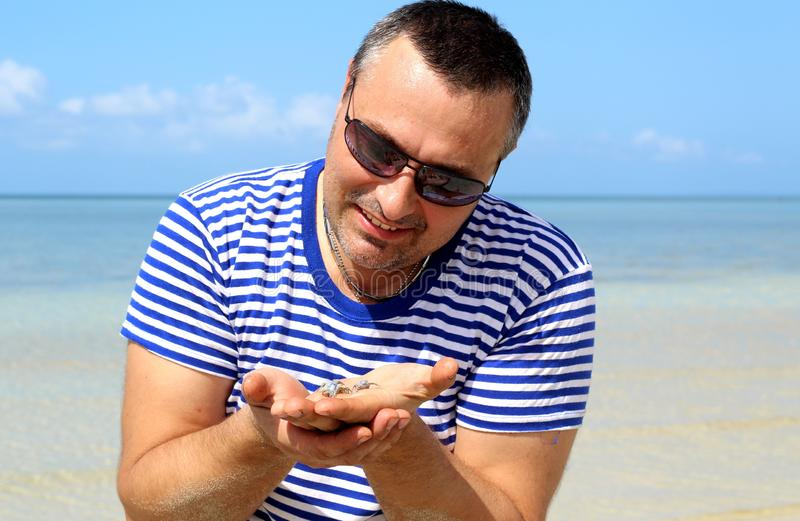 Man on the sea with crabs on the palm. Image of a man on the background of the sea with crabs on the palm stock images