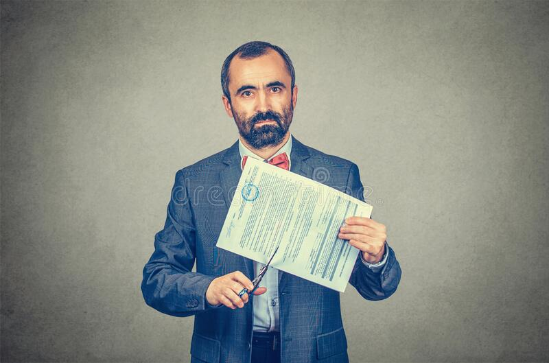 Image of man cutting a document with scissors. Cancel a contract concept. Image of man cutting a document with scissors while looking at you camera serious stock photography