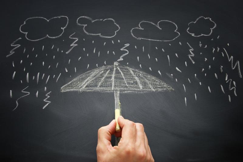 image of a man drawing an umbrella for protection against rain and storm. security and insurance concept. stock images