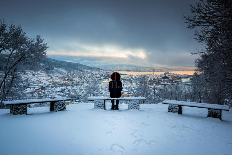 Winter Scene with A Lone Man Sitting on Snowy Benches Overlooking Bergen City Center in A Storm. Image of a man looking at Bergen city center taken from Mount stock image