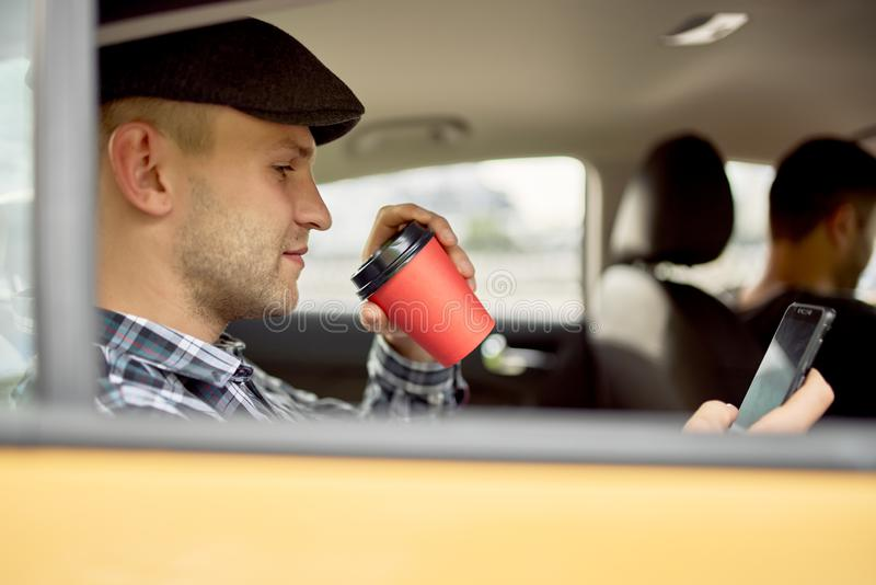 Image of man with phone and glass of coffee sitting in back seat in taxi. In afternoon royalty free stock images