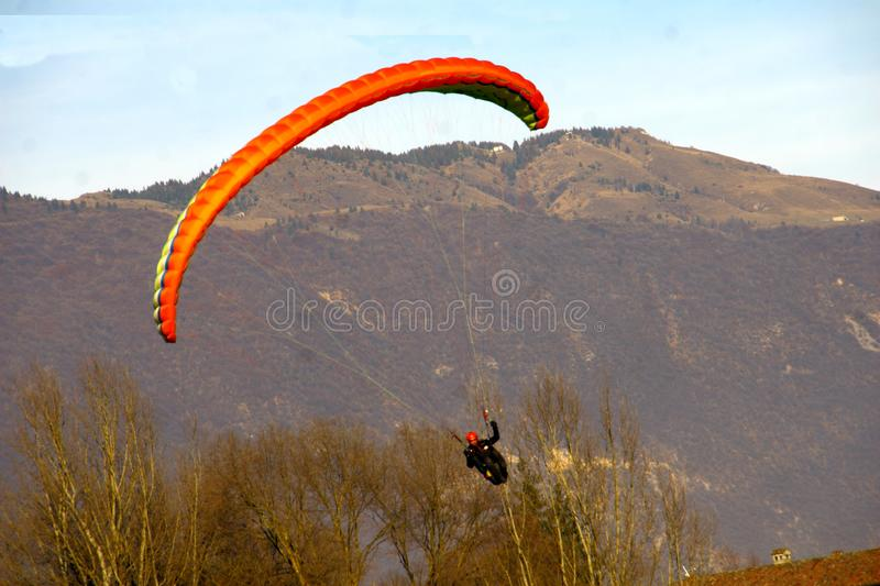 Image of man practicing parachuting over mountain landscape royalty free stock image