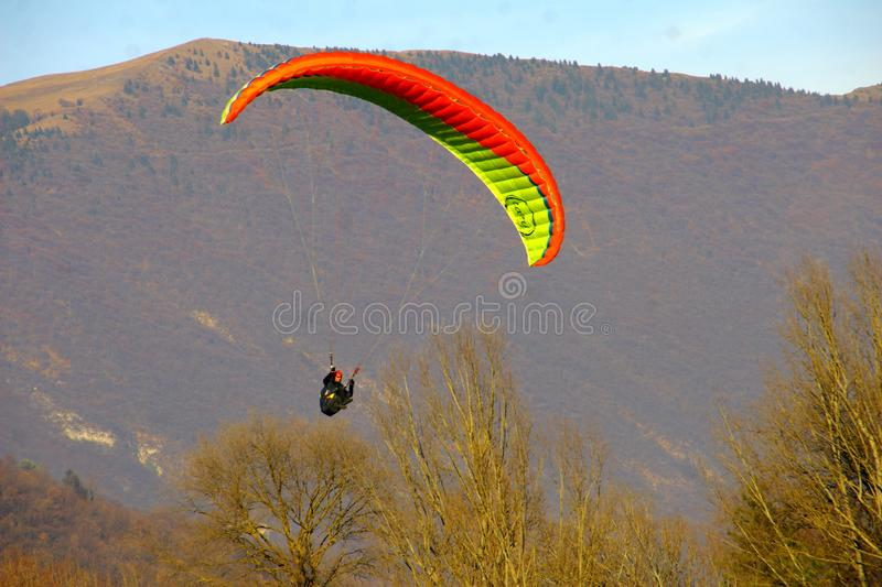 Image of man practicing parachuting over mountain landscape royalty free stock images