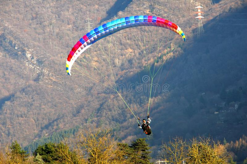 Image of man practicing parachuting over mountain landscape stock photography