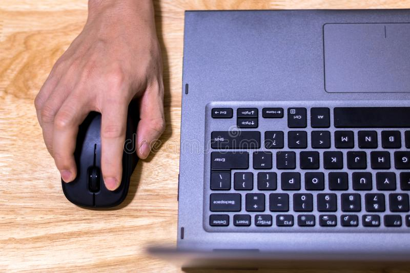 Hand Using Computer Mouse and Laptop on Desk stock photo
