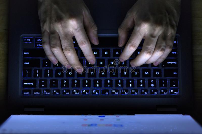 Hands Typing Laptop Keyboard In The Dark. Image of a man's hands working late with laptop at night in the dark, taken from above stock photos