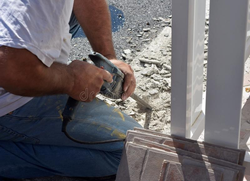 Image of man worker holding ceramic tile drill machine while drilling old tiles stock image