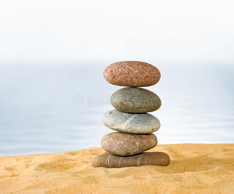 Image of many stones on a water background. Stones in the sand on the beach against the sea royalty free stock image