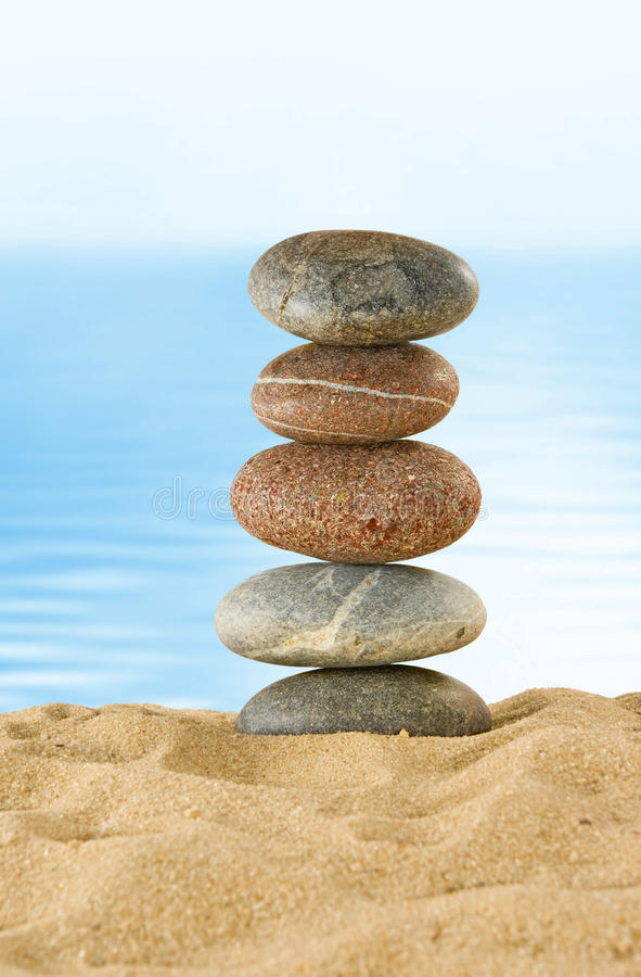 Image of many stones on a water background. Stones in the sand on the beach against the sea royalty free stock photos