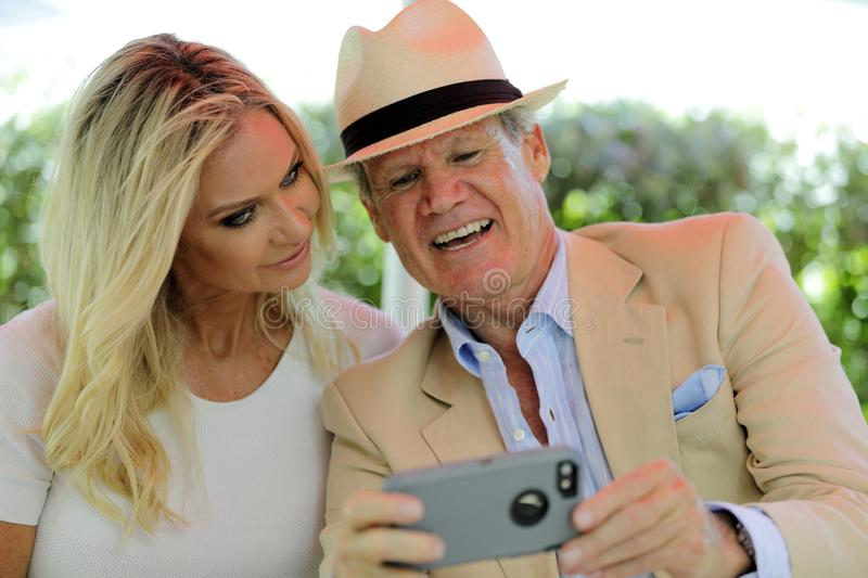 Mature couple looking at photos on a smart cellphone and smiling royalty free stock photos