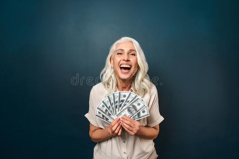 Mature happy old woman holding money. royalty free stock image
