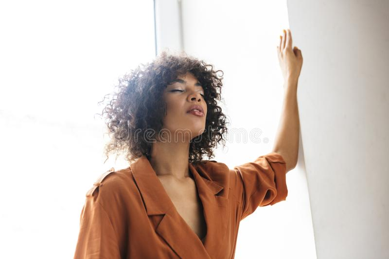 Image of Meditator pretty african woman posing with closed eyes. Near the wondow royalty free stock image