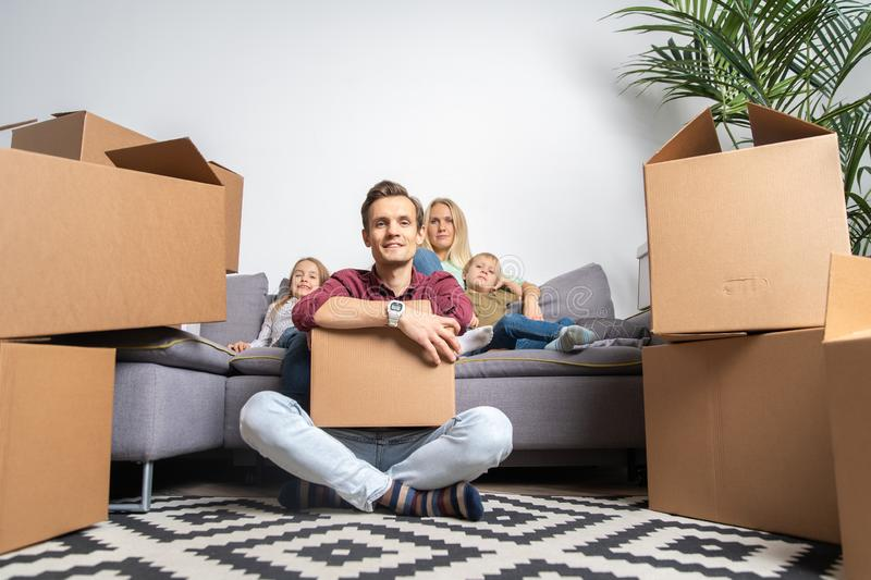 Image of man sitting on floor and women with boy and girl sitting on gray sofa among cardboard boxes. Image of men sitting on floor and women with boy and girl stock photo