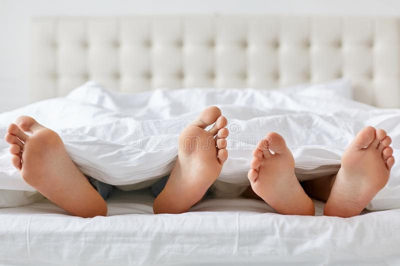 Image of man and woman bare feet under blanket in bedroom. Unrecognizable husband and wife spend free time in comfortable bed, enj. Image of men and women bare stock image