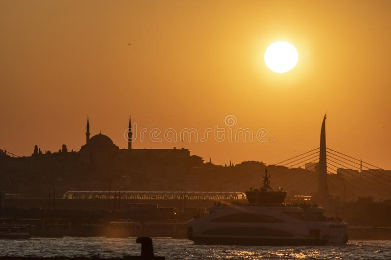 Image of metro bridge and steamship during sunset over Istanbul sea. The sun shines on the background royalty free stock photos