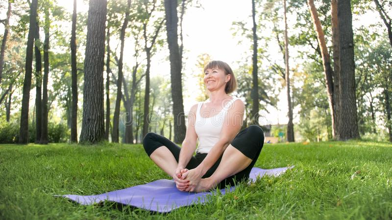 Photo of middle aged smiling woman practicing yoga and meditating at park. Woman stretching and doing fitness on mat at royalty free stock photography