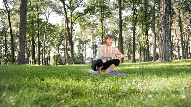 Photo of middle aged smiling woman practising yoga asana. Persong meditating in nature. Balance and harmony of body and stock photography