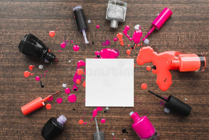 Image of mockup on wooden background with nail polishes. Place for the inscription in the women`s theme. Girlish glamorous image royalty free stock photo