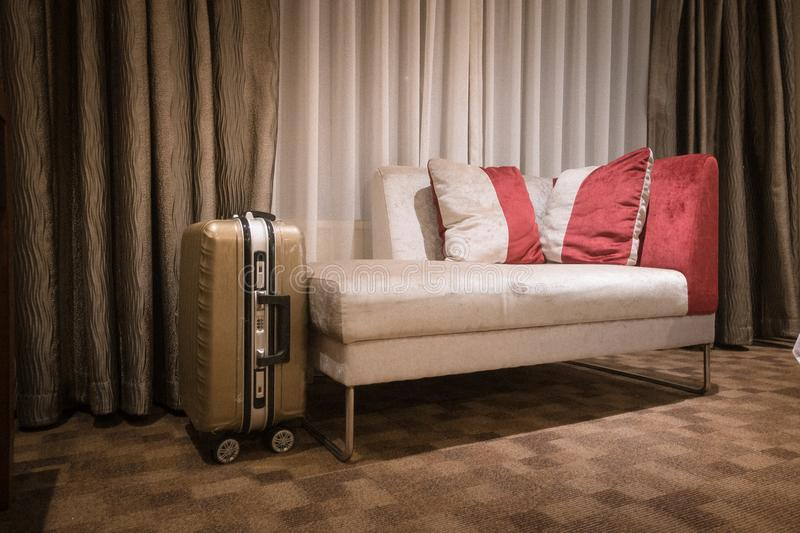 Interior of a hotel room with sofa and luggage. An image of a modern five star hotel master bedroom with a luggage next to sofa.horizonal color format, nobody in royalty free stock photo