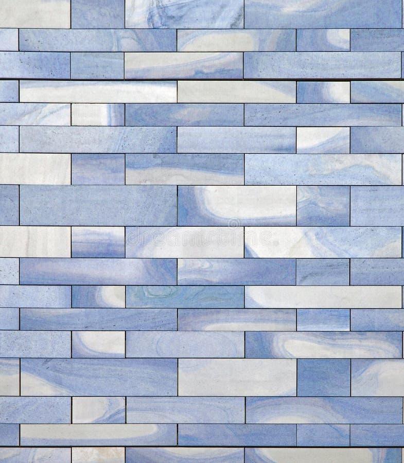Image modifiée la tonalité bleue d'un mur en pierre avec une surface texturisée et des rangées modelées géométriques des blocs photo stock