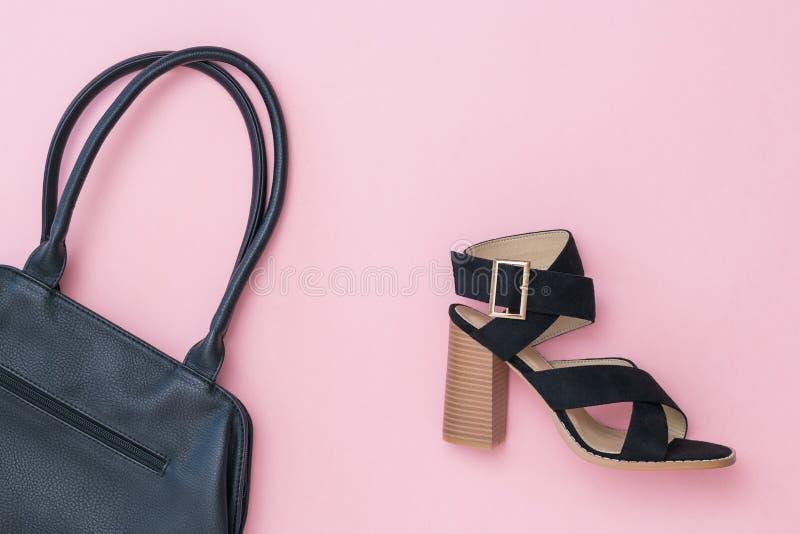 Image modifiée la tonalité d'une chaussure et d'un sac noir des femmes de couleur sur un fond rose photo stock