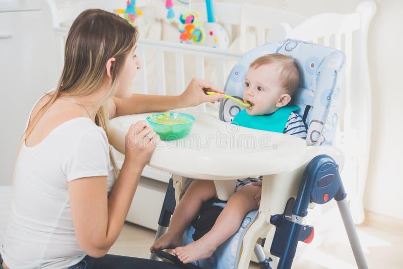 Image modifiée la tonalité de 10 mois de bébé garçon s'asseyant dans le highchair au salon et mangeant du gruau photo libre de droits