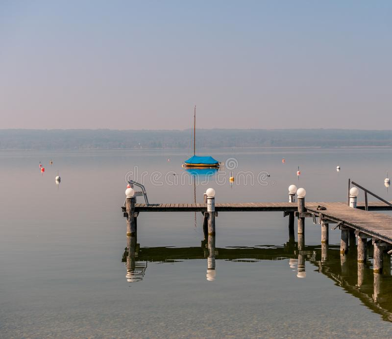 Image of mothballed sailing boat on a lake with wodden private pier in the foreground royalty free stock photos