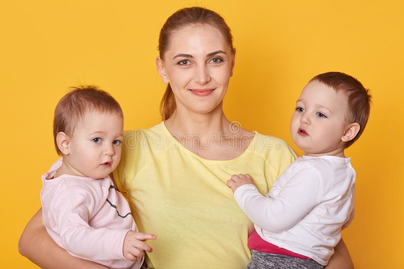 Image of mother with kids, two daughters in casual clothes, beautiful young woman with little twins standing in photo studio royalty free stock images