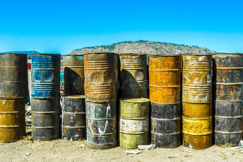 Image of old oil barrels in piles. Image of multi-colored, rusty and old oil barrels in piles with a blue sky and sunny day in Mexico stock images