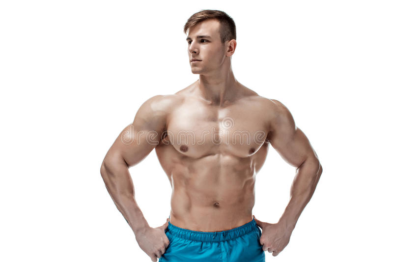 Image of muscle man posing in studio. Strong Athletic Man showing muscular body and sixpack abs isolated on white background stock image