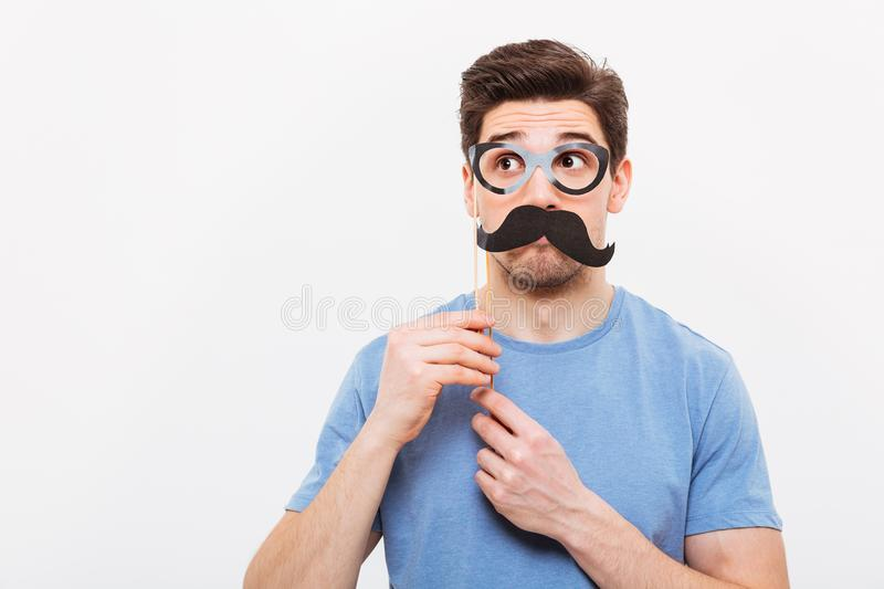 Image of Mystery man in fake mustache and eyeglasses. Looking away over grey background stock images