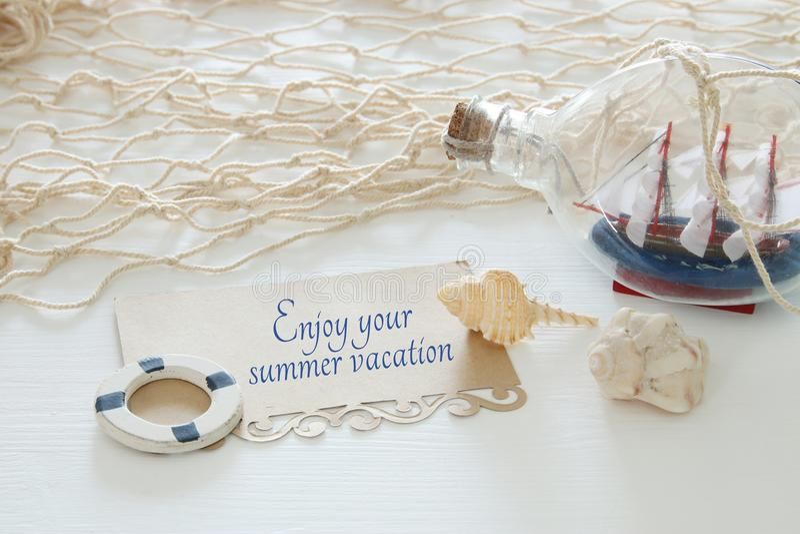 image nautique de concept avec le bateau à voile et la note décoratifs blancs : APPRÉCIEZ VOS VACANCES D'ÉTÉ photographie stock libre de droits