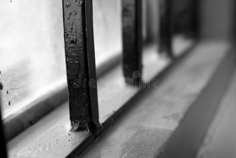 Image noire et blanche d'un carreau de fenêtre avec les grils en acier images libres de droits