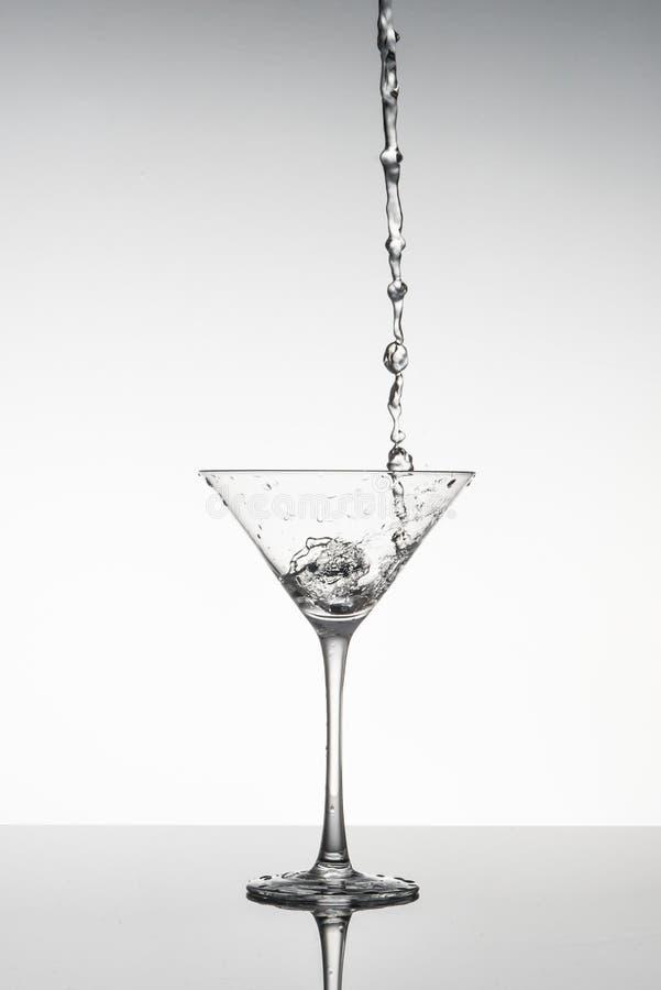 Image noire et blanche d'un verre de Martini avec le liquide versant dans lui images libres de droits