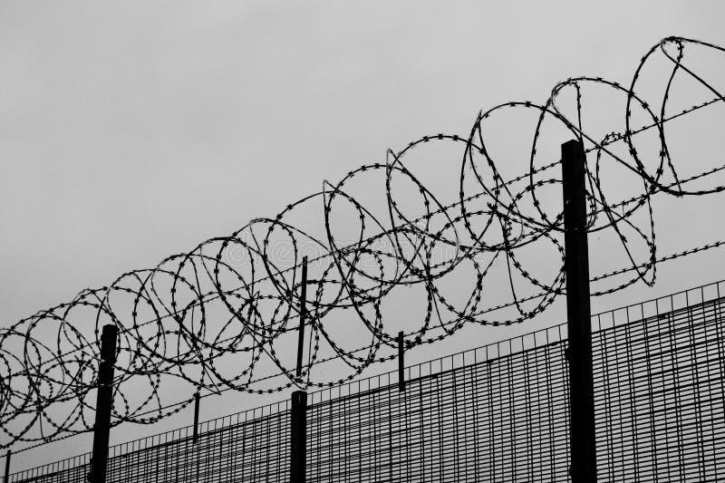 Image noire et blanche d'une barrière avec le barbelé - un concept de prison, emprisonnement photos stock