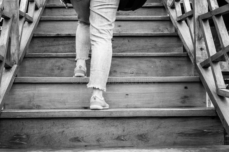 Image noire et blanche d'une femme marchant vers le haut des escaliers images stock