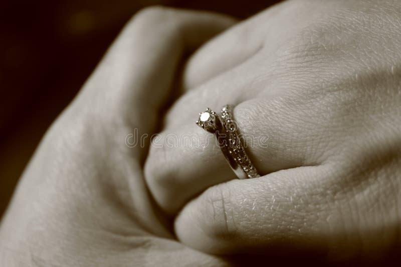 Image noire et blanche de deux mains se touchant avec des anneaux de mariage sur le fond noir images libres de droits