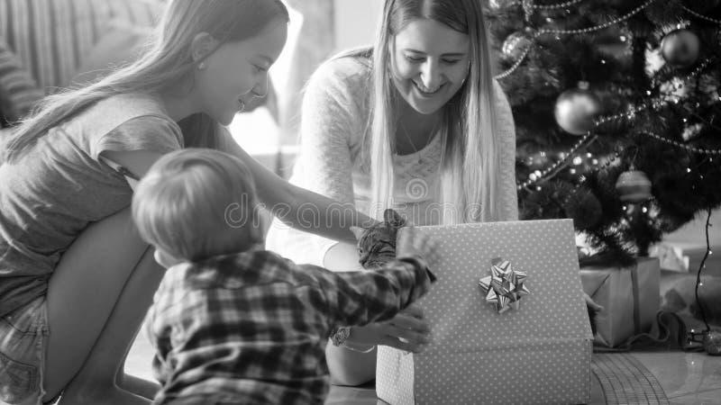 Image noire et blanche de la famille de sourire gaie regardant sur le chat marchant hors du boîte-cadeau de Noël photographie stock