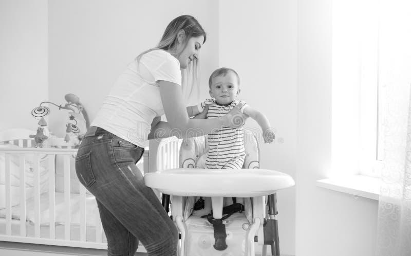 Image noire et blanche de mère d'oyung asseyant son fils de bébé dans le highchair pour l'alimentation photos libres de droits