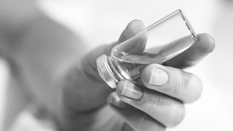 Image noire et blanche de main femelle tenant l'ampoule avec le medictaion photos libres de droits