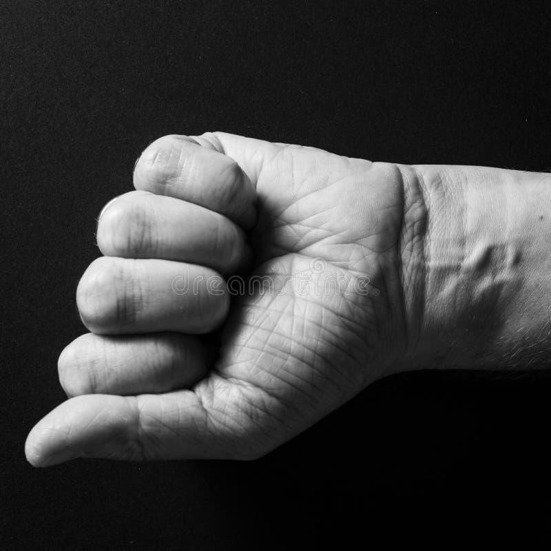Image noire et blanche du poing serré et du poignet de l'homme, d'isolement sur un fond noir avec le feu de position dramatique photos libres de droits