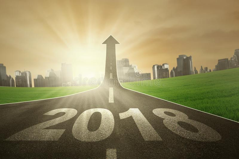 Empty road with numbers 2018 and upward arrow. Image of numbers 2018 and upward arrow on the end of road. Symbolizing better future royalty free stock images