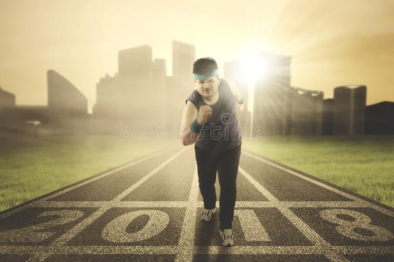 Obese man running on the track royalty free stock images