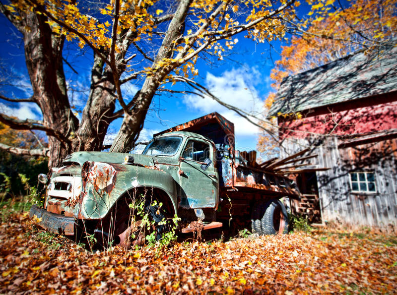 Image of an old abandoned truck and a barn royalty free stock image