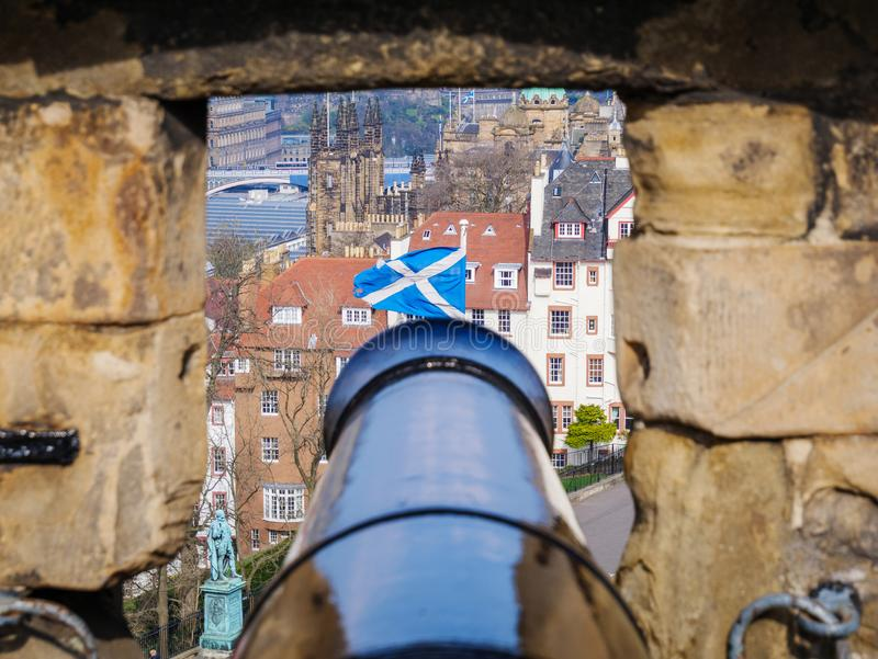 Image of old black canon aiming from castle on scottish flag. Image of old black canon aiming from Edinburgh castle on scottish flag close up royalty free stock photo
